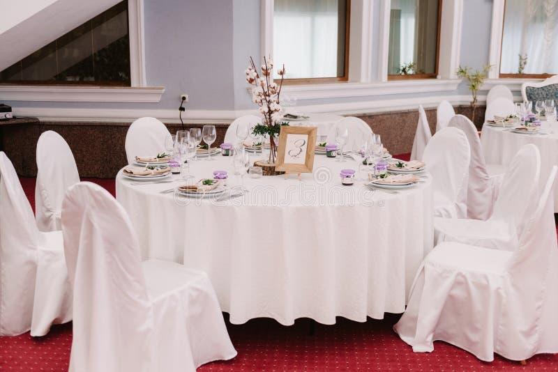 Ślubny gościa stół, dekorujący z bukietem i położeniami fotografia royalty free