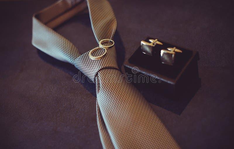 Ślubny krawat, złociste obrączki ślubne i cufflinks, ciemny wygodny kolor obraz stock
