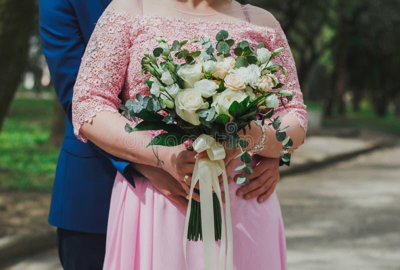 Ślubny para uścisk each inny Fornal ręki na panny młodej talii Curvy kobiecie w menchiach zasznurowywają wieczór suknię Ślubny bu zdjęcie stock