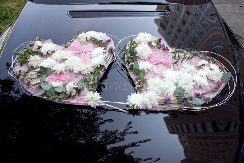 Ślubny samochód Dekorował z kwiatami w postaci dwa serc zdjęcia stock