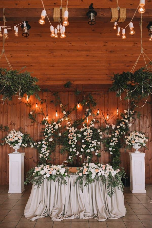 Ślubny stołowy bankiet dekorujący z kwiatami i roślinami, retro lampy na drewnianym tle obrazy royalty free