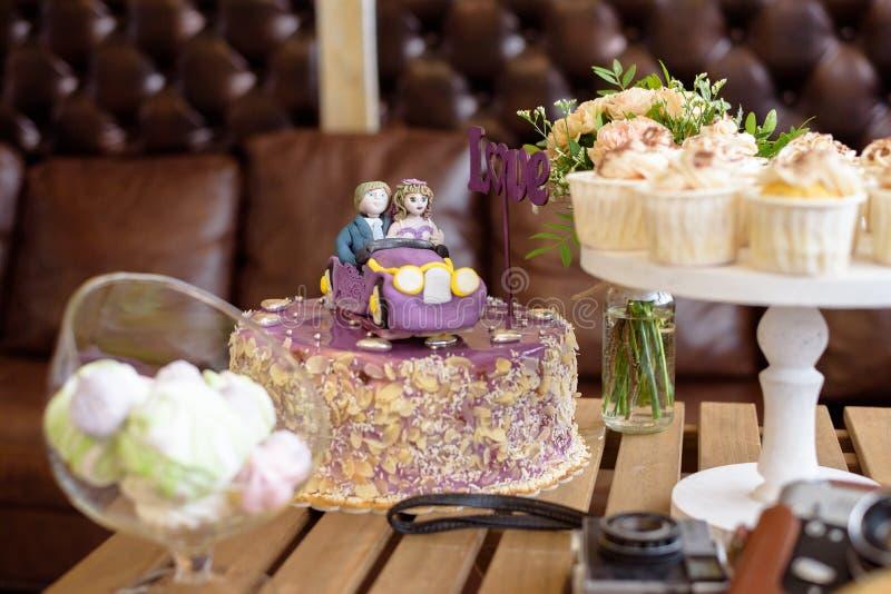 Ślubny tort z numer jeden miłością para w samochodzie, zbliżenie, Ślubne babeczki obraz stock