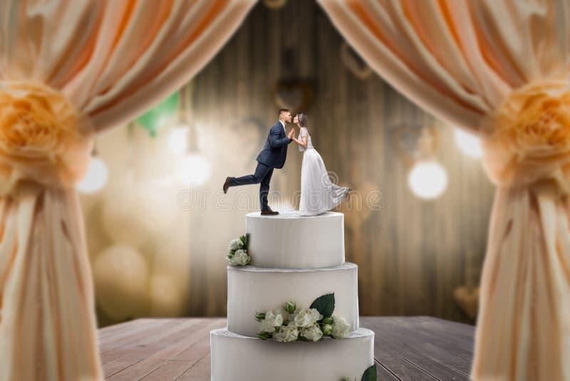 Ślubny tort z państwem młodzi na wierzchołku obraz royalty free