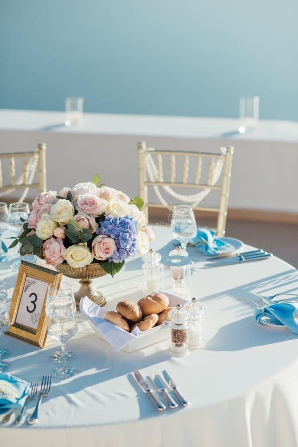 Ślubny wystrój stoły na wyspie Santorini w złota, błękitnych i bielu kolorach, fotografia royalty free