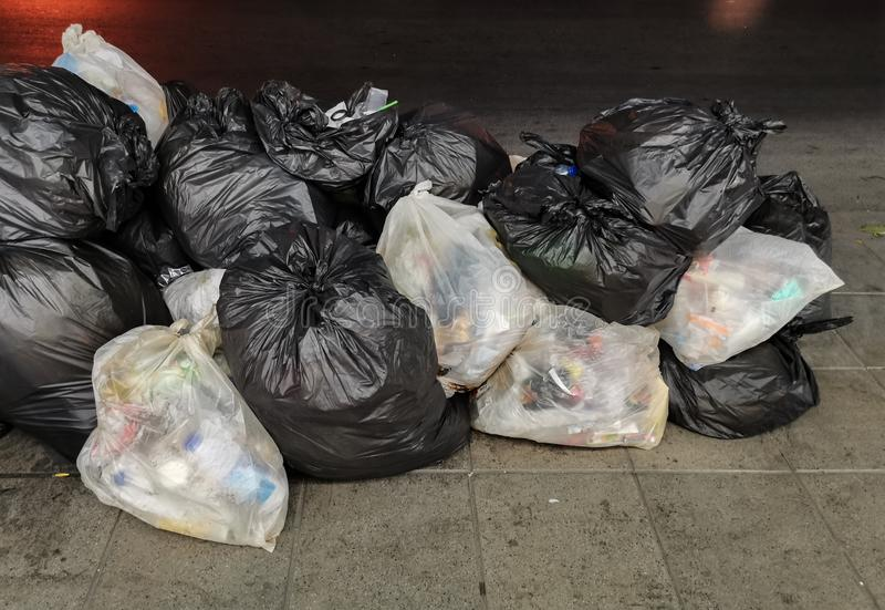Śmieci - śmieciarski rozsypisko w czarny i biały torbie stawia wpólnie na footpath, pobocze w mieście, Czekać na śmieci fotografia stock