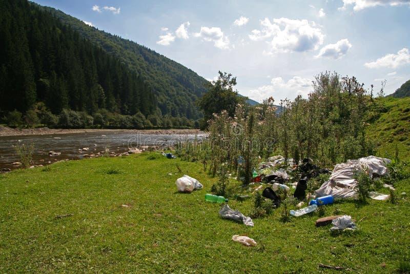 Śmieci na brzeg rzekim w górach fotografia royalty free