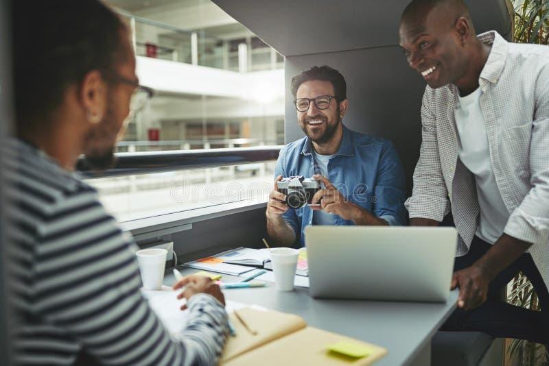 Śmiejąca się grupa projektantów pracujących razem nad projektem fotograficznym zdjęcie stock