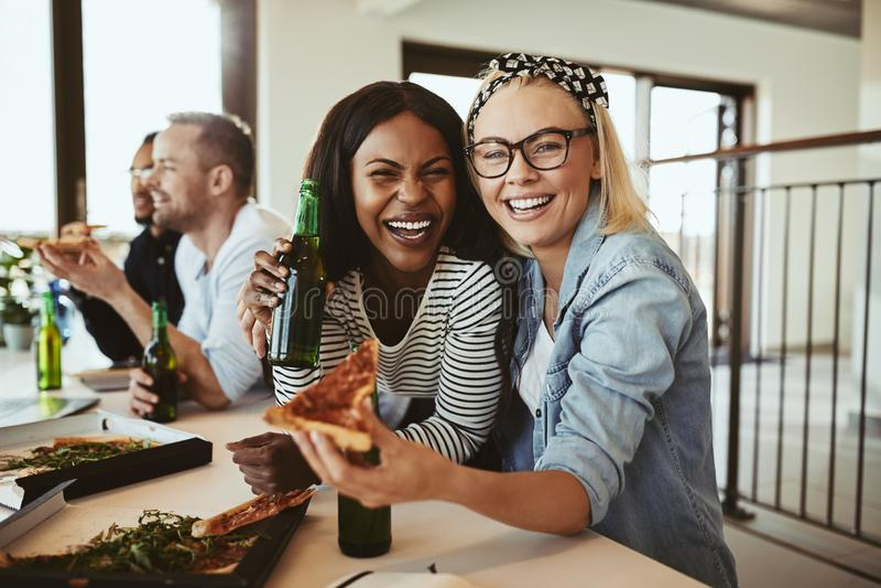 Śmiejące się biznesmenki pijące piwo i pizzę z kolegami af obraz stock