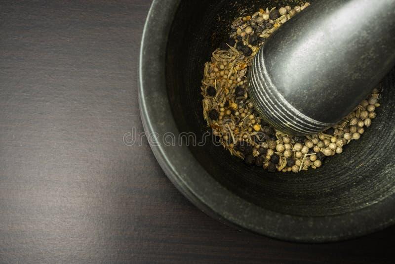 Śmiertelniczki i tłuczka withspices na czarnym drewnianym tle fotografia stock