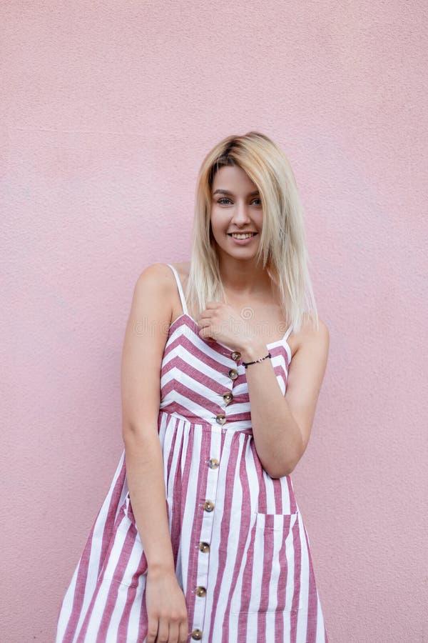 Śmieszna ładna młoda blond kobieta w różowi modni pasiaści sundress z uśmiechu pozytywnymi pozami blisko rocznik menchii ściany fotografia stock