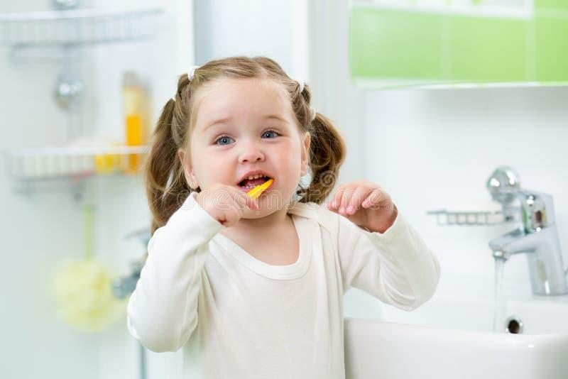 Śmieszna śliczna dziecko dziewczyna szczotkuje zęby w łazience zdjęcia stock