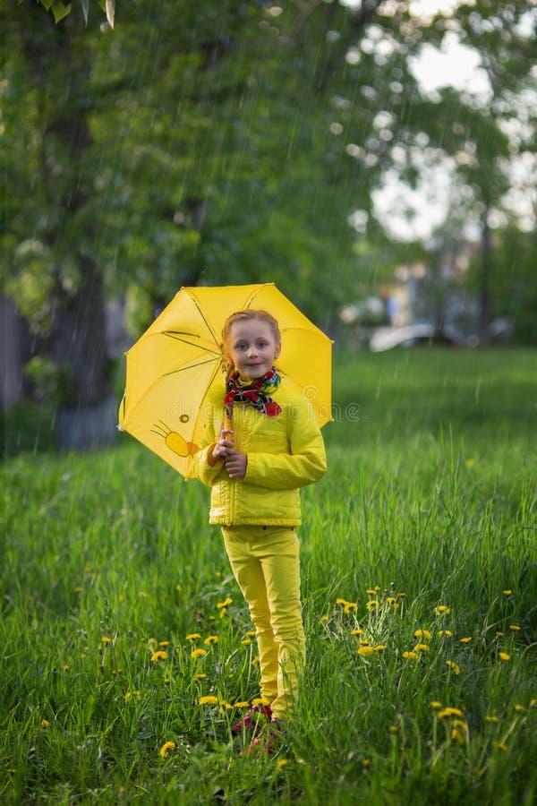 Śmieszna śliczna dziewczyna jest ubranym żółtego żakiet trzyma kolorowego parasol bawić się w ogródzie deszczu i słońca pogodą na obrazy stock