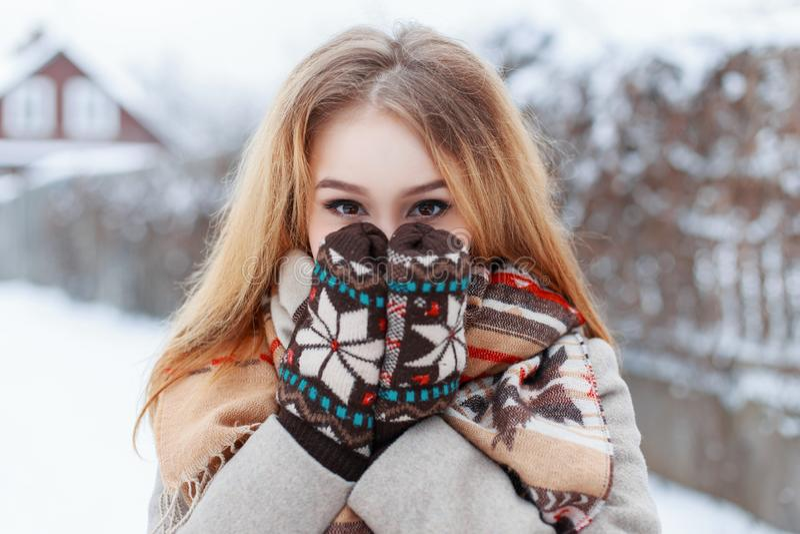 Śmieszna śliczna młoda kobieta z brązów oczami zakrywa jej twarz z jej rękami w zim woolen ciepłych mitenkach Elegancka szczęśliw obrazy royalty free