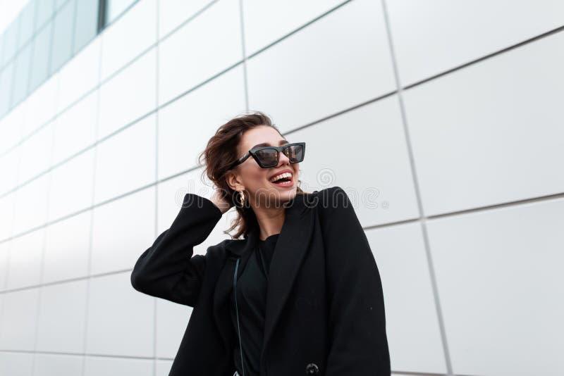 Śmieszna atrakcyjna szczęśliwa młoda modniś kobieta w pozytywnym uśmiechu w modnym czarnym żakiecie w eleganckich ciemnych okular fotografia royalty free