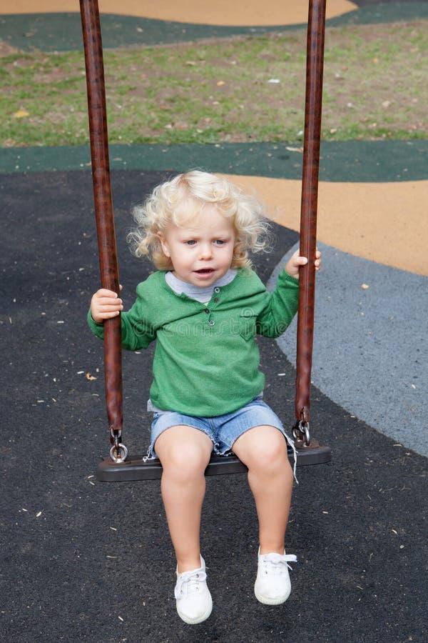 Śmieszna blond chłopiec jazda na huśtawce fotografia stock