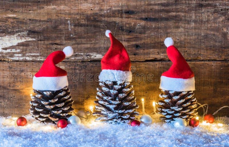 Śmieszna Bożenarodzeniowa dekoracja z rożkami ozdobnymi z czerwonymi Santa Claus kapeluszami na śniegu z światłami i piłkami zdjęcia stock