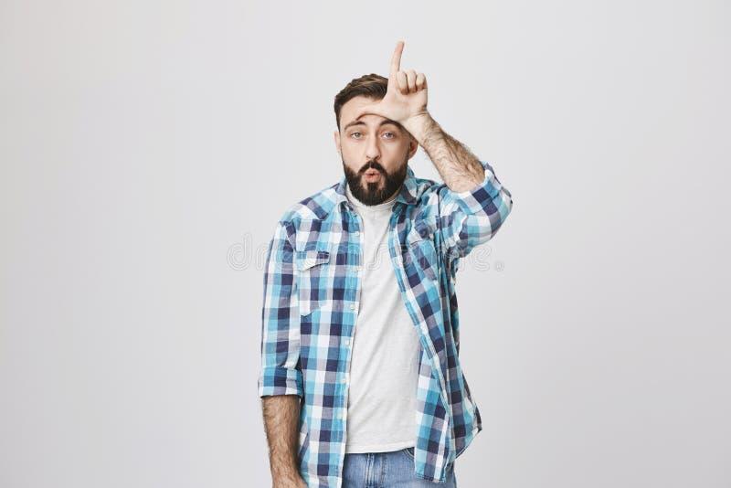 Śmieszna caucasian samiec z brodą i wąsem robi zabawie somebody, trzyma rękę na czole z zwyciężonym gestem i zdjęcie stock