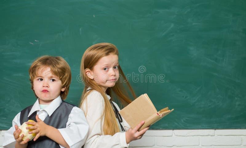 Śmieszna chłopiec i śliczna mała dziewczynka wskazuje w górę blackboard na kosmos kopii Blackboard t?o Szko?a dzieciaki dzieci fotografia stock