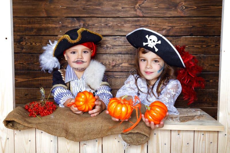 Śmieszna chłopiec i dziewczyna w piratów kostiumach w studiu z scenerią dla Halloween obrazy royalty free