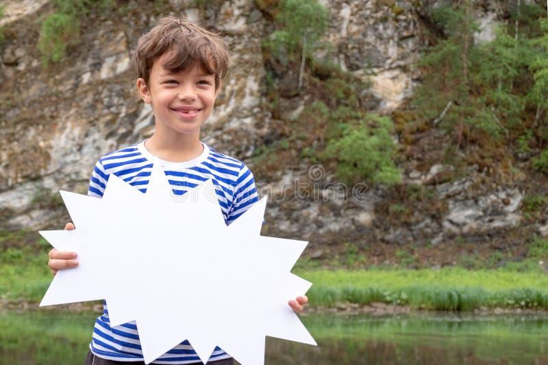 Śmieszna chłopiec w pasiastej żeglarz koszula jest roześmiana i trzymająca białego znaka przed on Rabaty i promocje, podróż i obraz royalty free
