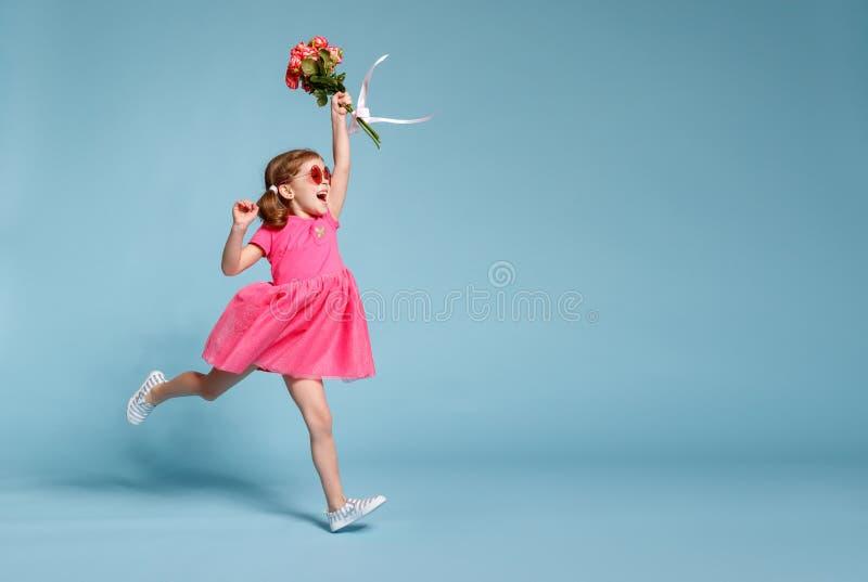 Śmieszna dziecko dziewczyna biega i skacze z bukietem kwiaty na kolorze zdjęcia stock