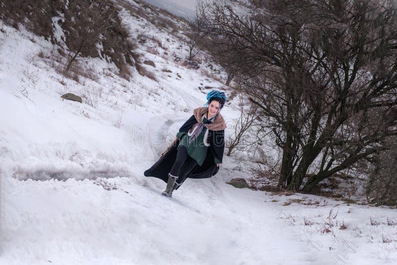 Śmieszna dziewczyna iść na drodze i ono uśmiecha się Szczęśliwa Viking kobieta z kordzikiem w czerni długiej salopie z futerkiem  obraz stock