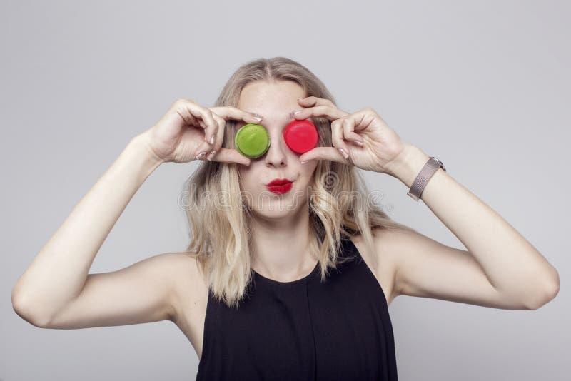 Śmieszna dziewczyna robi twarzom z dwa macaroons umieszczającymi zamiast oczu Dziewczyna kędzierzawego blondyn i patrzeje seksown obraz royalty free