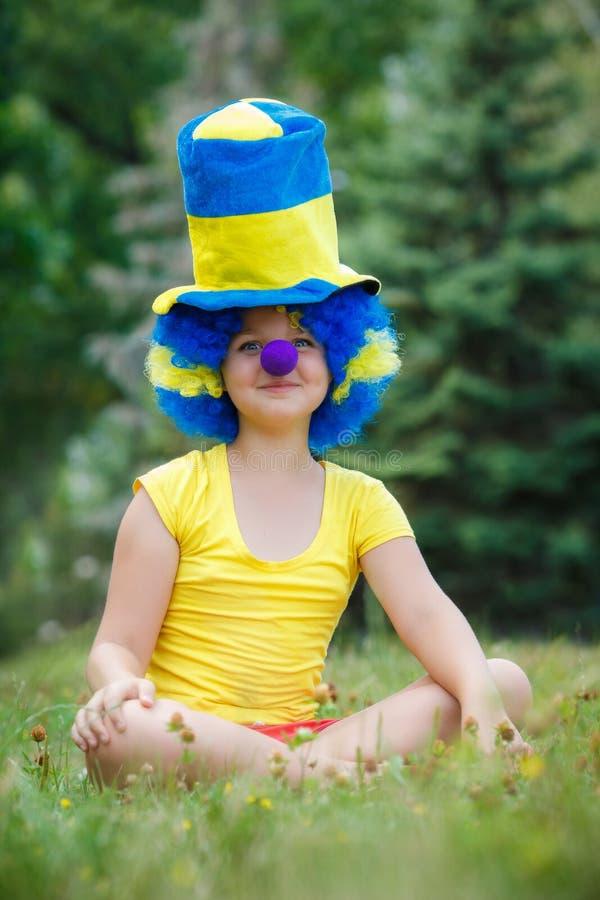 Śmieszna dziewczyna w błazen peruce z błękitnym nosem obrazy royalty free