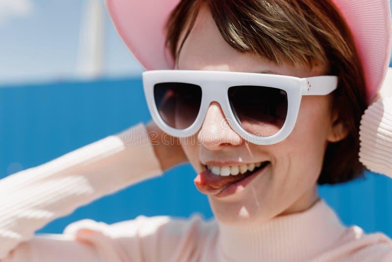 Śmieszna dziewczyna w białych okularach przeciwsłonecznych i różowym naliczku pokazuje jej jęzor na słonecznym dniu outside zdjęcia stock