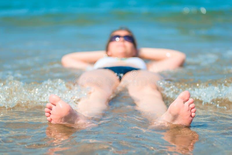 Śmieszna fotografia piękny dziewczyny lying on the beach w morzu obraz royalty free