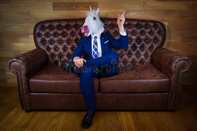 Śmieszna jednorożec jest usytuowanym na kanapie w eleganckim kostiumu obrazy royalty free