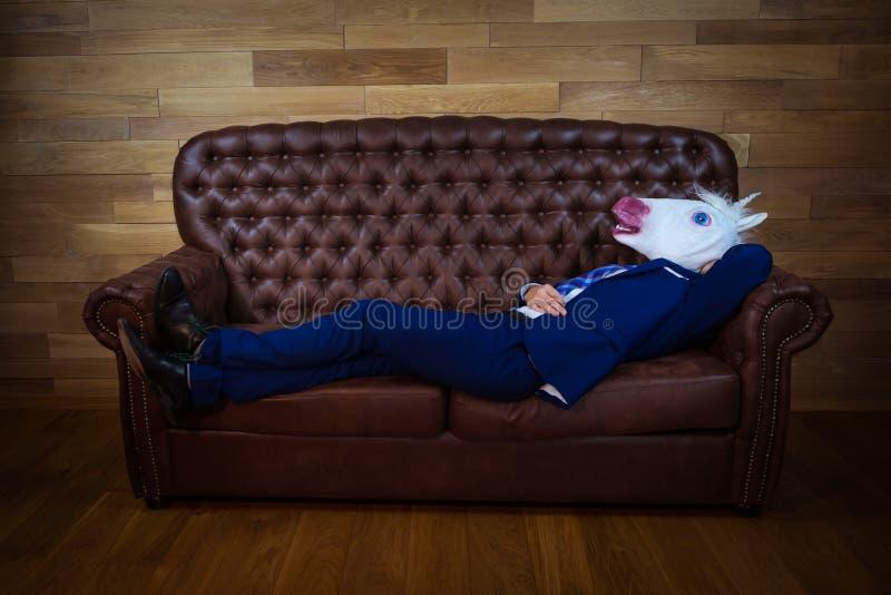 Śmieszna jednorożec w eleganckim kostiumu kłama na rzemiennej kanapie fotografia royalty free