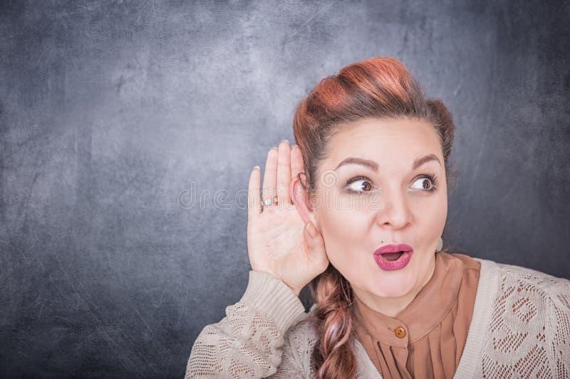 Śmieszna kobieta podsłuchuje na blackboard tle zdjęcia stock