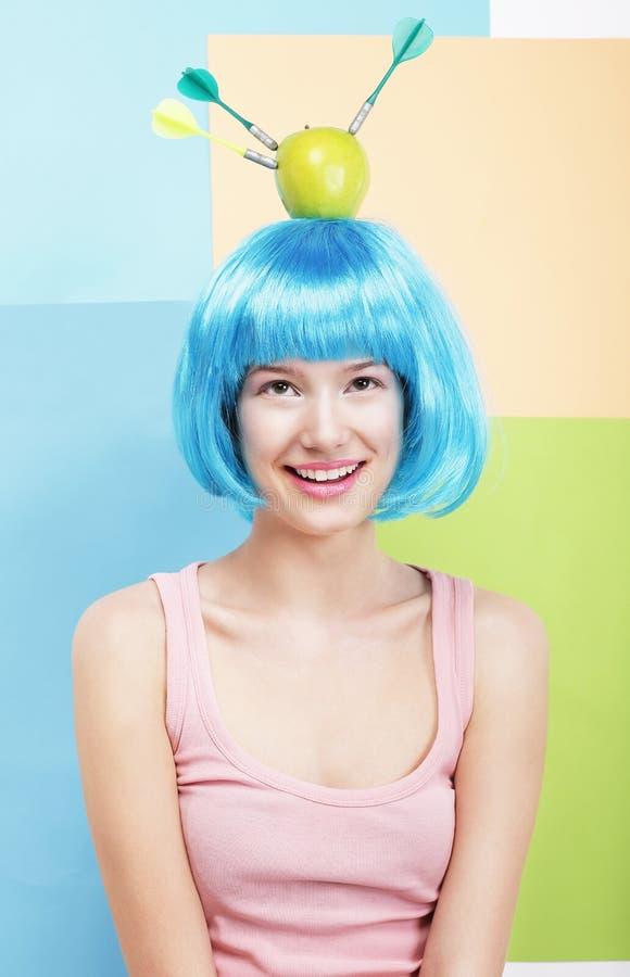 Śmieszna kobieta w Błękitnej peruce, Zielonym Apple i strzałkach, obraz stock