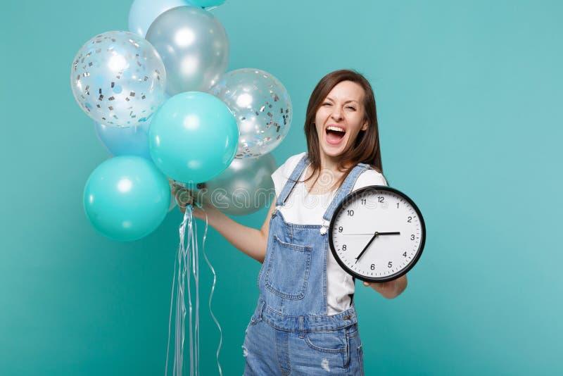 Śmieszna krzycząca młoda kobieta w drelichu mienia round odzieżowym zegarze i odświętność z kolorowymi lotniczymi balonami odizol fotografia royalty free