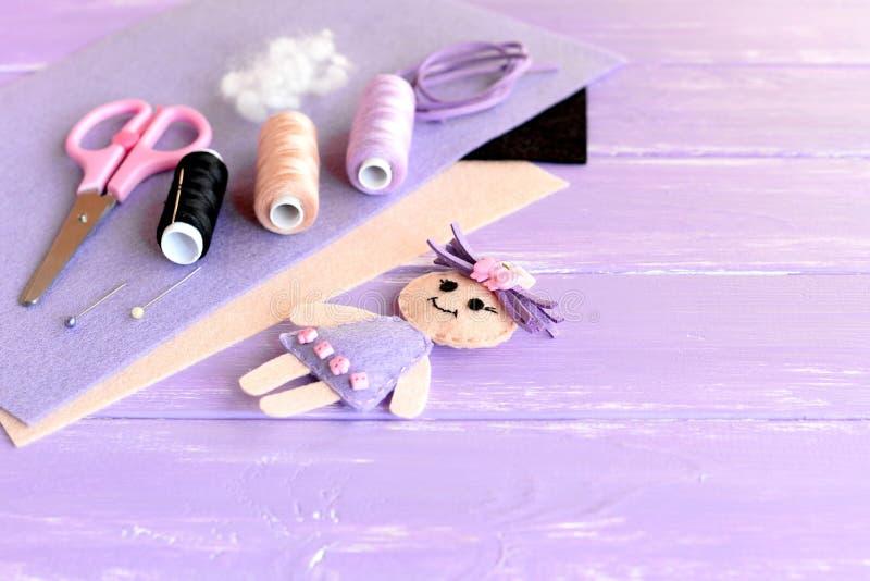 Śmieszna lala dekorująca z guzikami, nić set, igła, szpilki, nożyce, płascy kawałki odczuwany na drewnianym tle z pustym miejscem zdjęcia stock