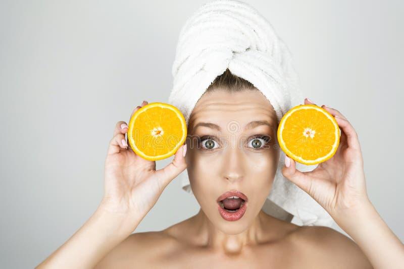 Śmieszna młoda kobieta patrzeje zaskakującego odosobnionego białego tło w białym ręczniku na jej kierowniczych mienie pomarańczac obrazy stock