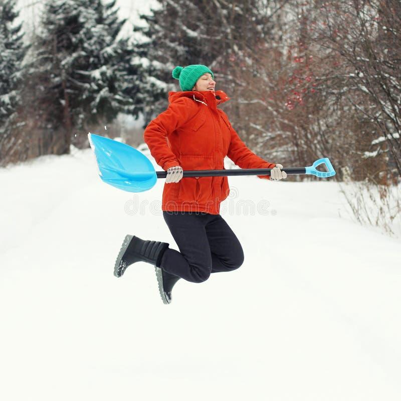 Śmieszna młoda kobieta skacze z śnieżną łopatą na wiejskiej drodze Zimy sezonowy pojęcie kwadrat obrazy stock