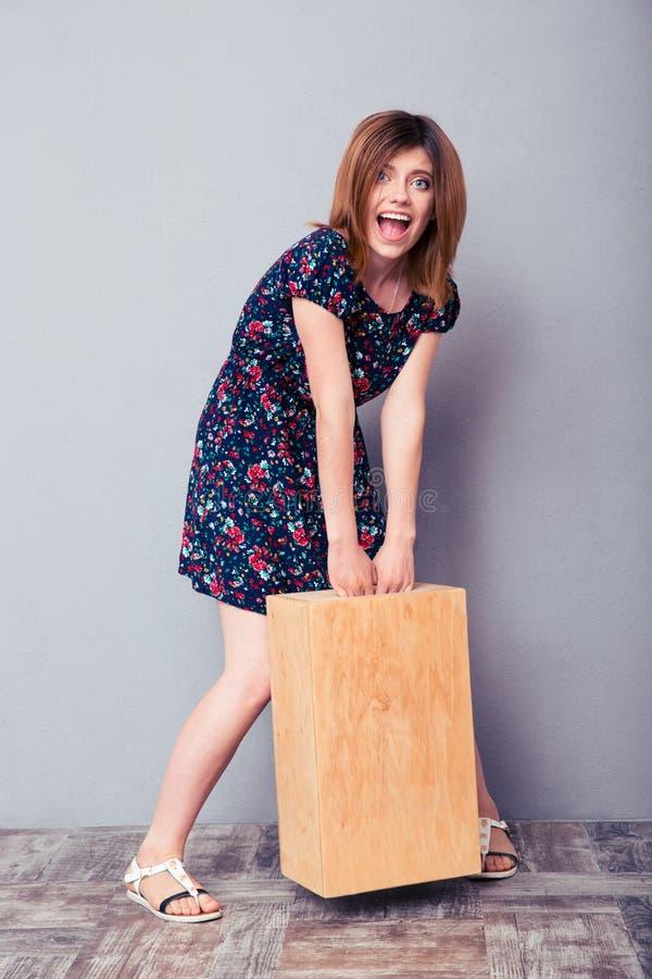 Śmieszna młoda kobieta trzyma drewnianego pudełko fotografia stock
