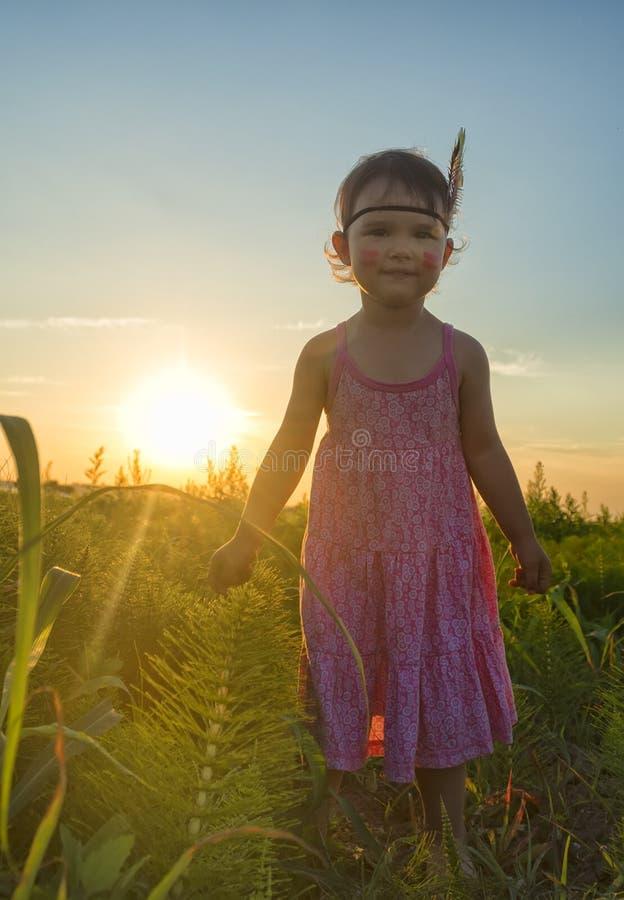 Śmieszna mała dziewczynka jako hindus z marakasami i piórkiem zdjęcia stock
