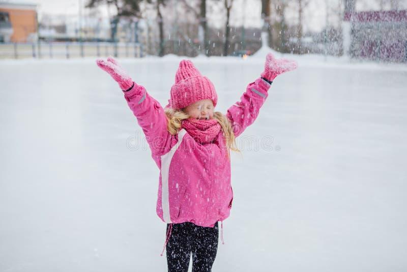 Śmieszna mała dziewczynka ma zabawę w pięknym zima parku podczas opadu śniegu fotografia royalty free