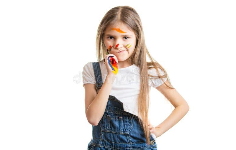 Śmieszna mała dziewczynka malował twarz pozuje nad białym tłem fotografia stock