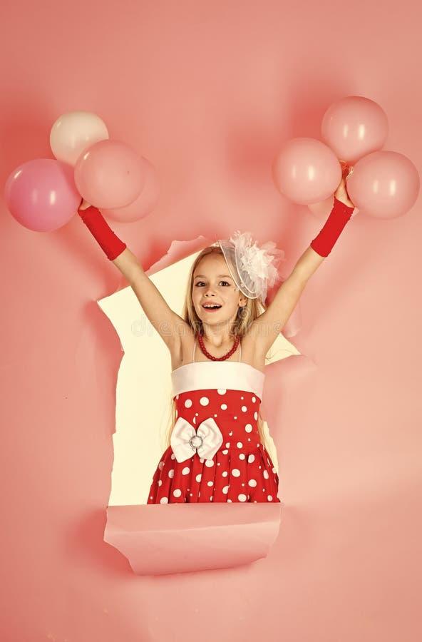 Śmieszna mała dziewczynka na tle jaskrawa menchii ściana Piękny dziecko ma zabawę z balonem Różowi i czerwoni kolory obrazy stock