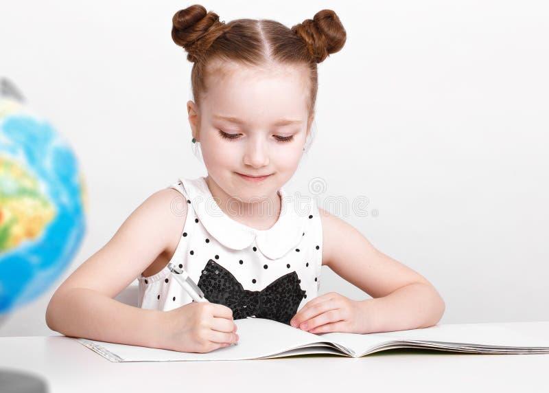 Śmieszna mała dziewczynka przy stołem równiarka zdjęcie stock