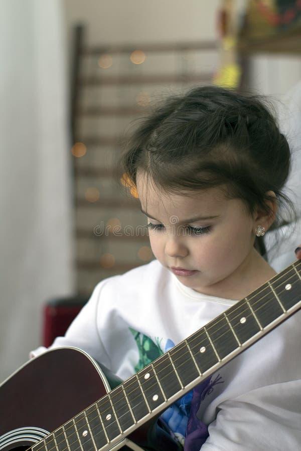 śmieszna mała dziewczynka trzyma gitarę w koszulce fotografia stock