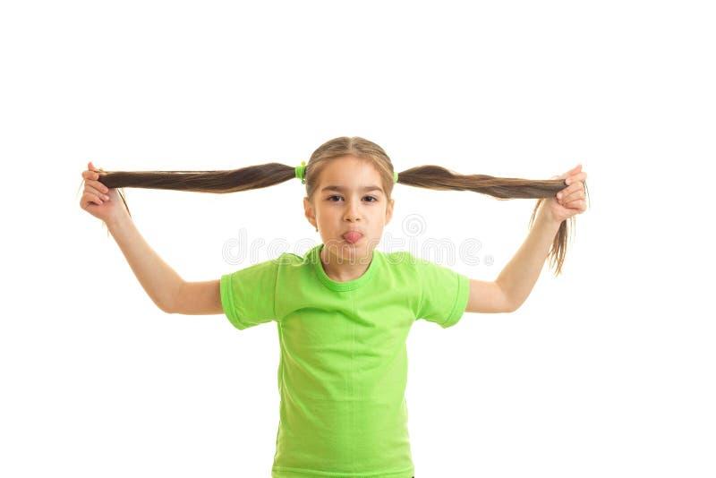 Śmieszna mała dziewczynka w zielonym koszulowym holdin jej ogony w rękach obrazy royalty free
