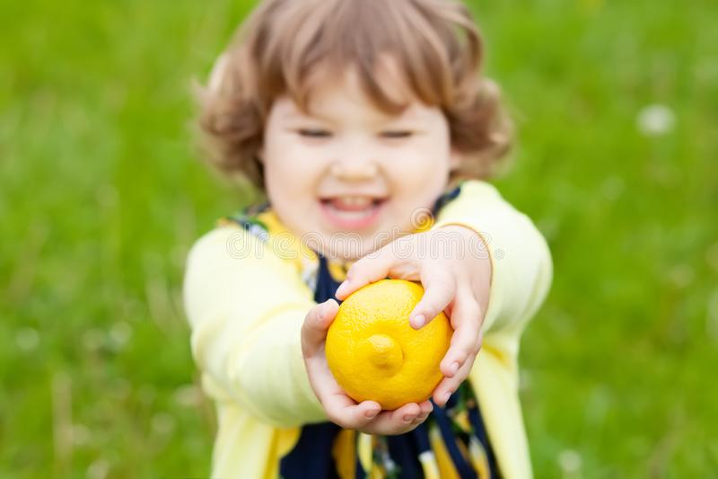 Śmieszna mała dziewczynka z cytryny owoc outdoors zdjęcia royalty free