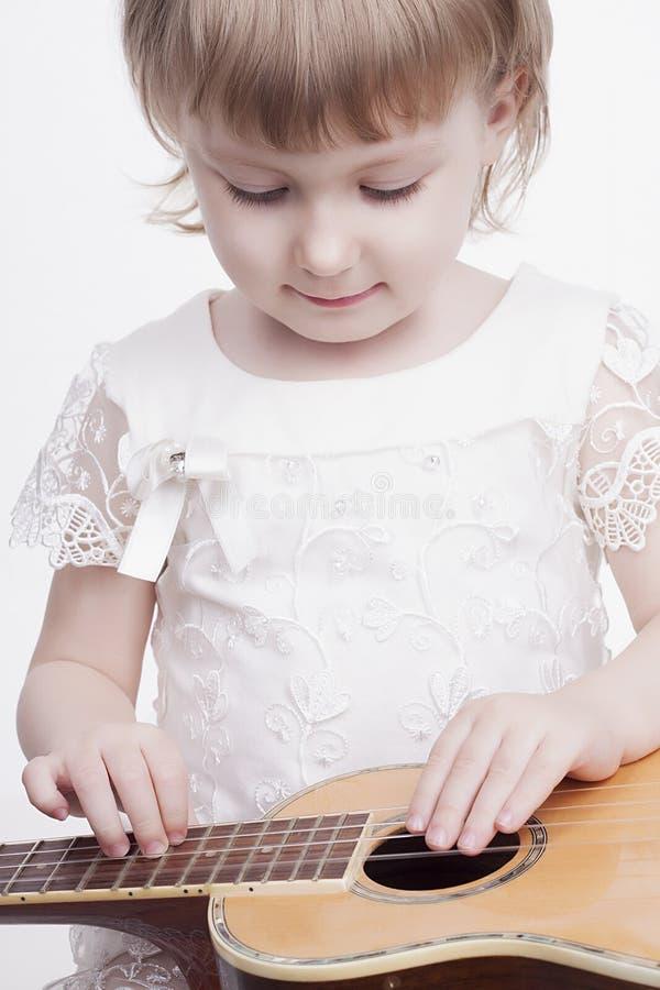 Śmieszna mała dziewczynka z gitarą obraz royalty free
