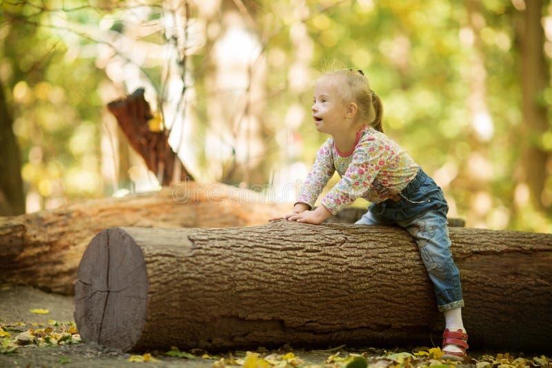 Śmieszna mała dziewczynka z puszka syndromu obsiadaniem na wielkiej beli fotografia royalty free