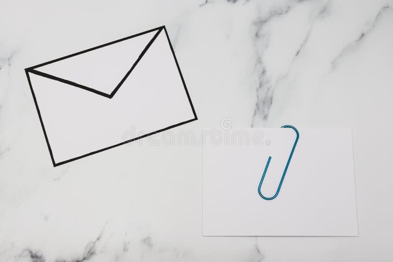 Śmieszna metafora inbox z emailem i doczepianie klamerka na realnym biurku odkrywamy zdjęcie stock